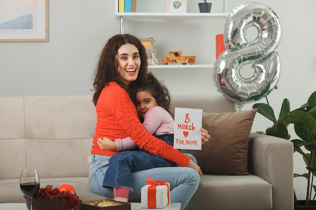 Happy mother with her little child daughter sitting on a couch holding greeting card smiling cheerfully and embracing in light living room celebrating international women's day march 8