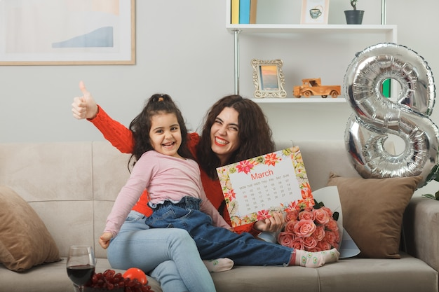 花の花束と3月8日の国際女性の日を祝う明るいリビングルームで元気に笑っている月の行進のカレンダーとソファに座っている彼女の小さな子供の娘と幸せな母