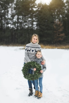 Счастливая мать с маленьким сыном, стоя на фоне зимнего леса на открытом воздухе