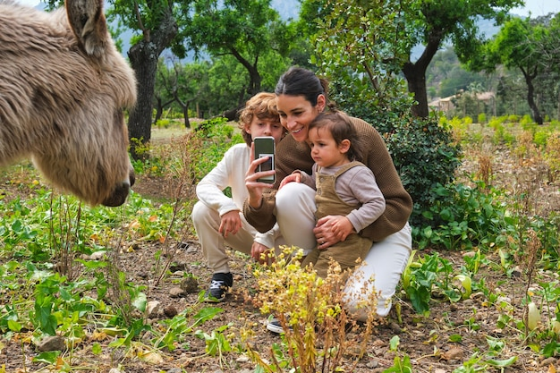 귀여운 당나귀 사진을 찍는 아이들과 함께 행복한 어머니
