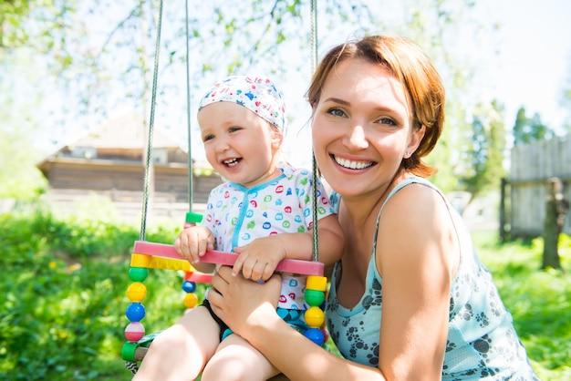 笑っている赤ちゃんと幸せな母親はブランコに座っています