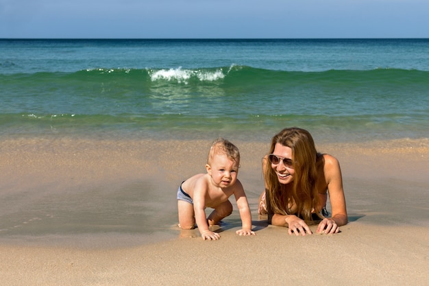 Happy mother with little baby on beach