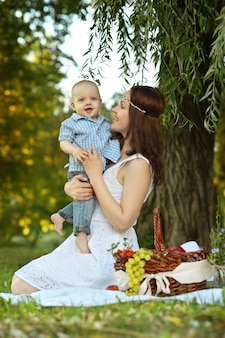 Happy mother with little son at the picnic in the park