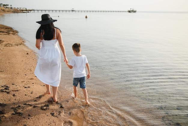 Счастливая мать с сыном гуляют по пляжу
