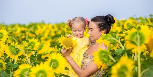 Счастливая мать с дочерью в поле с подсолнухами