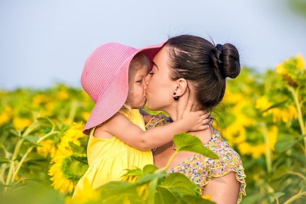 해바라기를 가진 분야에서 딸과 함께 행복 한 어머니