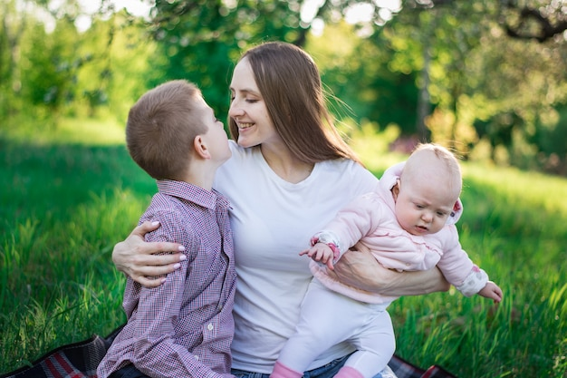 Happy mother with two children. brother and sister with mummy in the park. mom hugging her son and holds baby