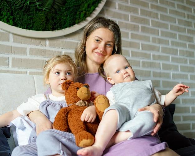 두 아이가 집에서 큰 침대에서 휴식을 취하는 행복한 어머니