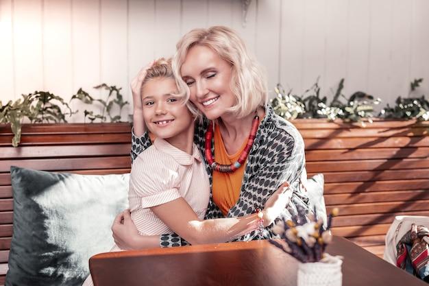 Счастливое материнство. милая радостная женщина обнимает свою любимую дочь, выражая свою любовь