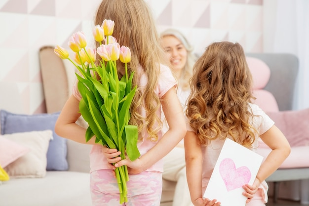 Happy mothers day. child daughters congratulate mom and give her a postcard and bouquet of flowers tulips in pink livingroom in their house.