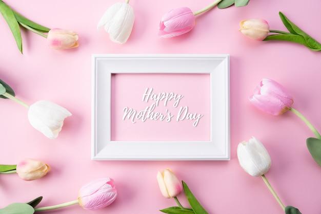 幸せな母の日の概念。ピンクのチューリップと額縁の平面図