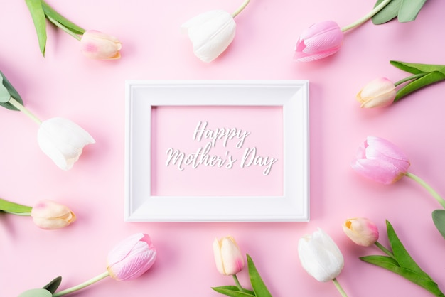 幸せな母の日の概念。ピンクのチューリップの花と白い額縁のトップビュー