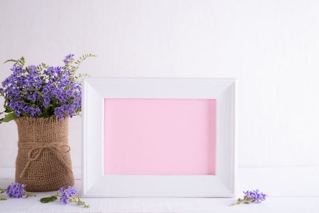 Happy mothers day concept. white picture frame with lovely purple flower in vase