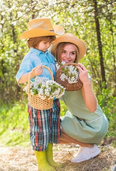 Happy mothers day. family farm. spend time together. lovely family outdoors nature background. farmers in blooming garden. my sweet baby. ranch concept. growing flowers. mother and cute son in hats.