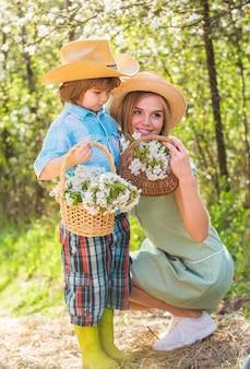 С днем матери. ферма семьи. проводить время вместе. прекрасная семья на открытом воздухе природа фон. фермеры в цветущем саду. моя сладкая детка. концепция ранчо. выращивание цветов. мать и милый сын в шляпах.