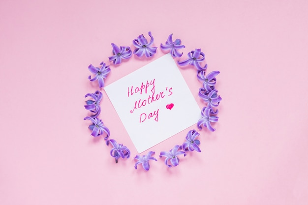 Happy mothers day greeting card with round frame of pastel purple hyacinth flowers