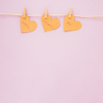 Happy mothers day inscription on hearts hanging on rope