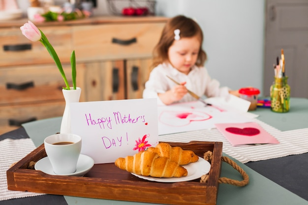 Happy mothers day inscription on table near girl painting heart