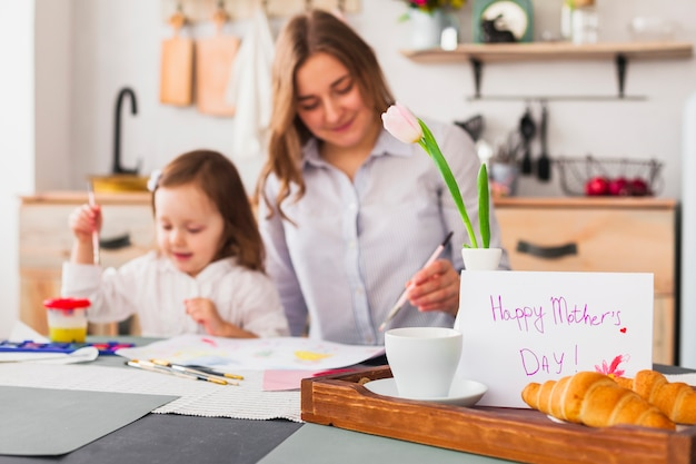 Happy mothers day inscription on table near painting daughter and mother