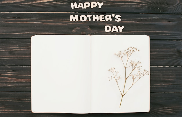 Happy mothers day inscription with flower branch on notebook