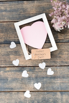 Happy mothers day inscription with flowers, paper hearts and frame
