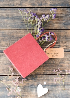 Happy mothers day inscription with flowers in small paper bag