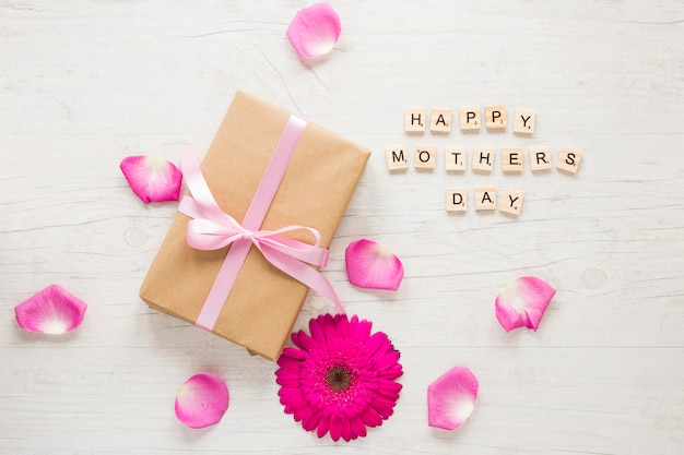 Happy mothers day inscription with gift box and gerbera