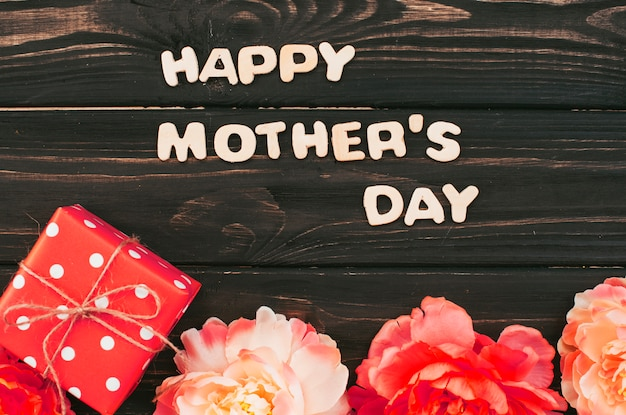 Happy mothers day inscription with gift and flowers