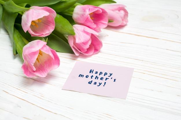 Iscrizione di happy mothers day con tulipani rosa