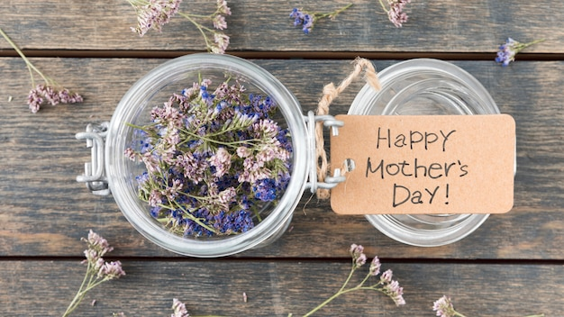 Happy mothers day inscription with small flowers in can
