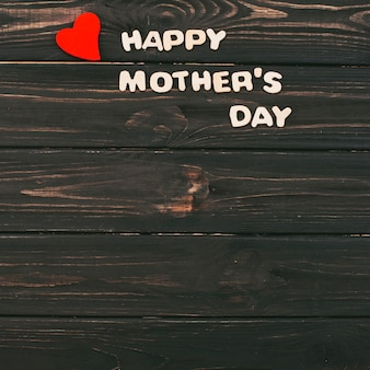 Happy mothers day inscription on wooden table