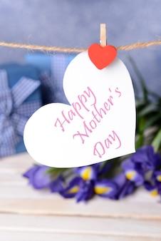 紫色の花と紙のハートに書かれた幸せな母の日のメッセージ