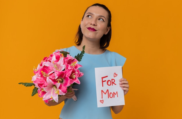 Happy mothers day. pleased pretty young mother holding bouquet of flowers and greeting card with text: for mom