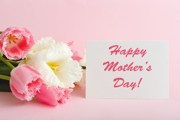 Happy mothers day text on gift card in flower bouquet on pink background.