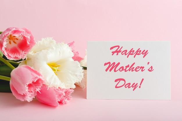 Счастливый день матери текст на подарочной карте в букет цветов на розовом фоне.