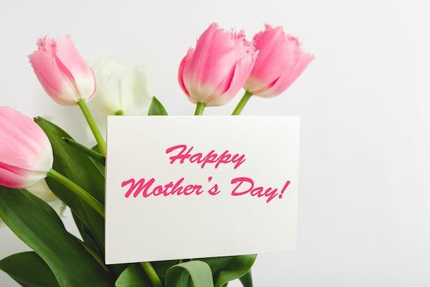 白い背景の花の花束のギフトカードに幸せな母の日のテキスト。お母さんのグリーティングカード。花の配達、女性のための花のおめでとうカード。ピンクのチューリップのグリーティングカード。