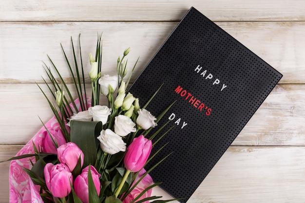 花の花束の近くボード上の幸せな母の日タイトル