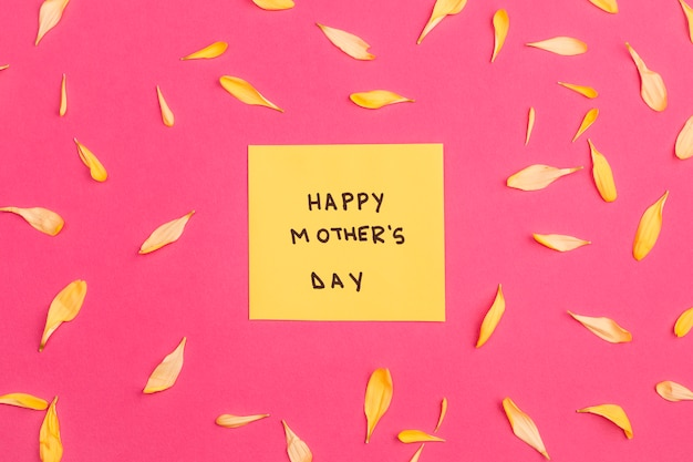 Happy mothers day title on paper among flower petals