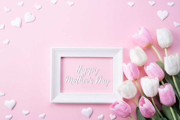 Happy mothers day with top view of pink tulip flowers and white picture frame