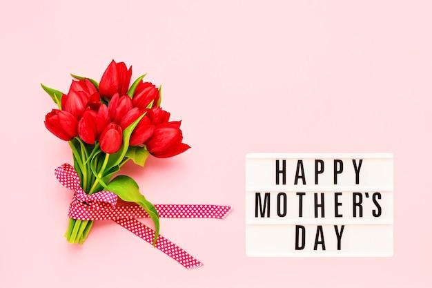 С днем матери написано в лайтбоксе и букет красных тюльпанов