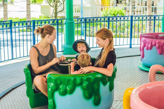 Happy mothers and little sons riding on a merry-go-round carousel together, smiling and having fun at a fair or amusement park. active family leisure with kids.