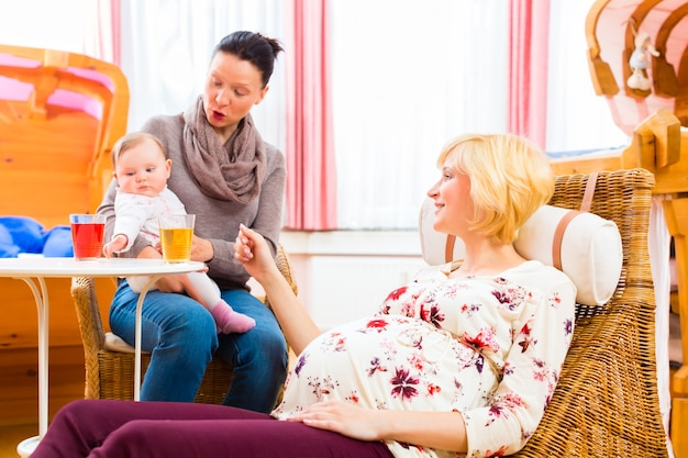 Happy mothers talking about pregnancy at midwife practice