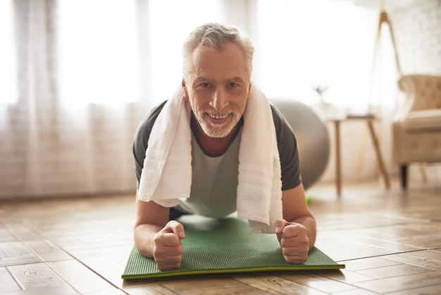 Happy motivated elderly man does plank exercise