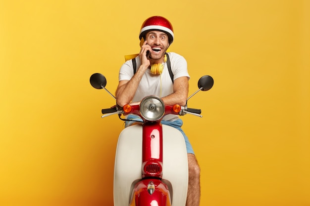 Happy motorcyclist poses on fast own transport, calls client via smartphone, travels on long distance, wears helmet, stereo headphones around neck, smiles at camera. male driver drives scooter