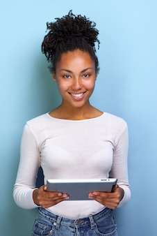 Happy mulatto woman standing with ipad looking at the camera and happily smile closeup