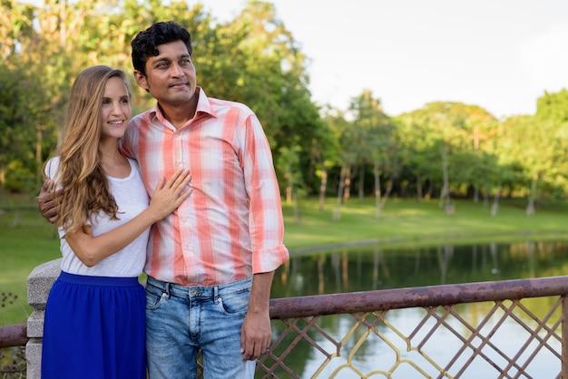 幸せな多民族のカップルの笑顔で、考えながら恋に
