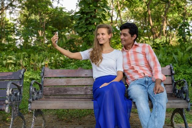Счастливая многоэтническая пара улыбается во время съемки селфи
