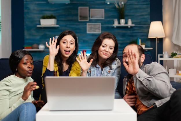 Happy multi-ethnic friends greeting her collegue during online videocall meeting using laptop webcam. group of multiracial people spending time together on couch late at night during party