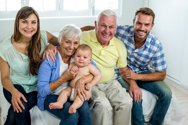 Happy multi-generation family on bed at home