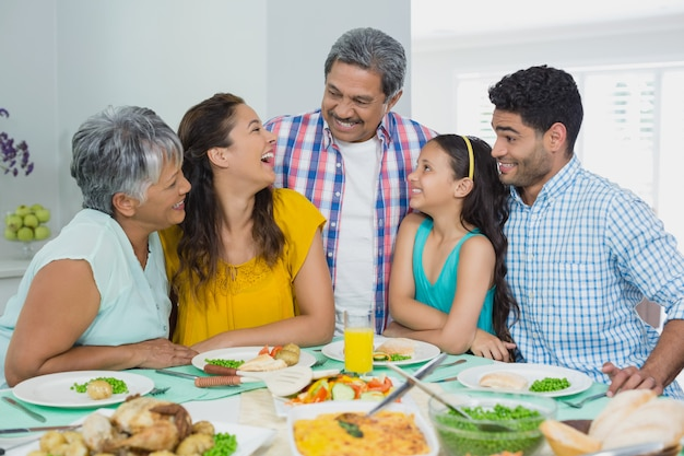 Happy multi generation family having meal on table at home